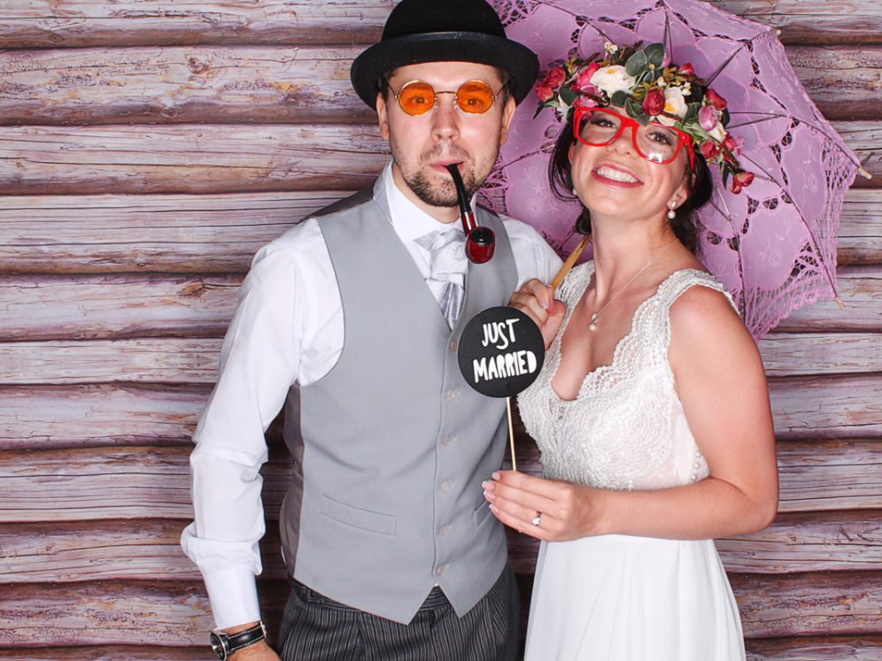 A photo of two people enjoying the little white photobooth