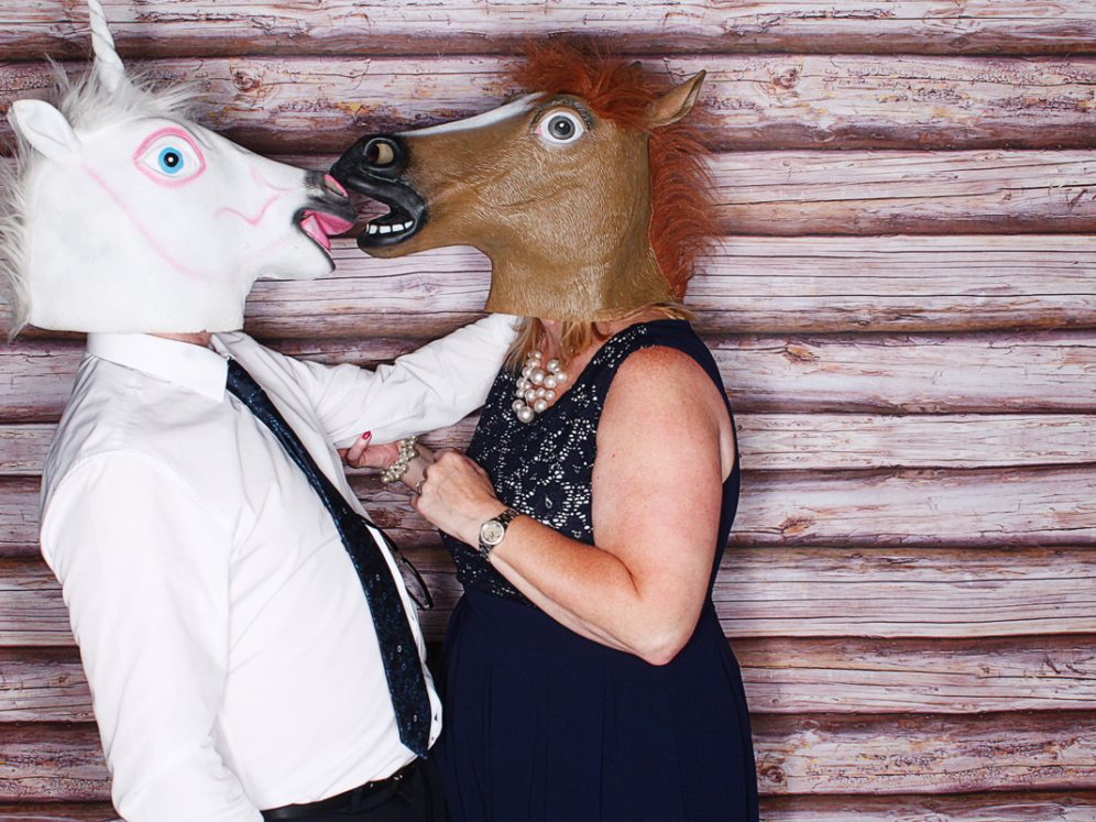A photobooth photo of two people in fancy dress horse heads