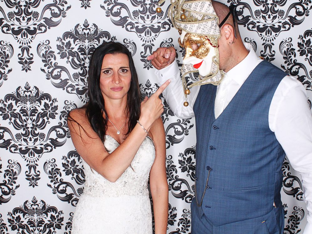 Man wearing fancy dress mask pointing at lady in white dress